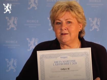 Erna Solberg viser frem lapp med navnet Odfjell